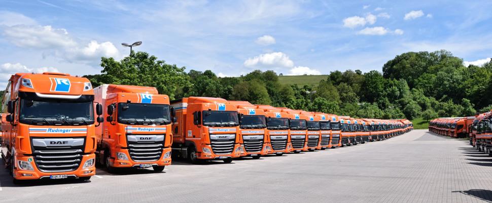 Man sieht das neue Betriebsgebäude der Spedition Rüdinger in Krautheim in Baden-Württemberg, daneben stehen links zwei LKW, rechts ein großer.. Der Himmel ist blau. Orange ist die dominante Farbe.
