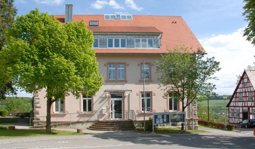 Das Rathaus von Krautheim in Baden-Württemberg. Links ein Baum in hellgrünem Frühlings-Laub. Rechts sieht man Fachwerk. Krautheim ist Sitz der Firma Rüdinger.