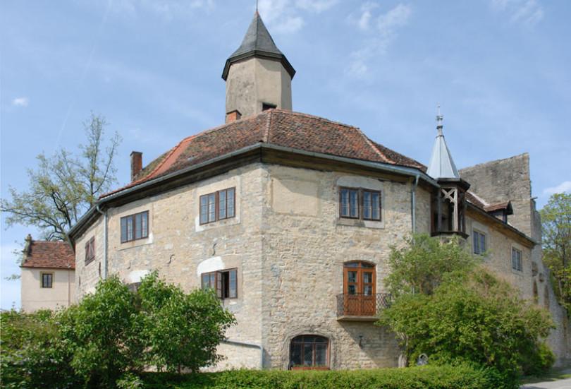 Man sieht den Wohntrakt der Burg Krautheim in Krautheim in Baden-Württemberg, unten ist hellgrünes Laub, oben fast blauer Himmel mit wenig weißen Wolken.