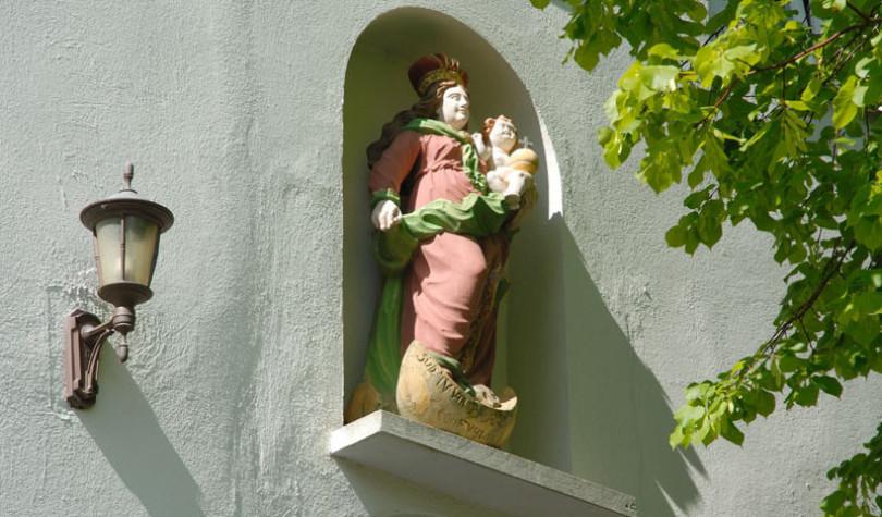 In Krautheim in Baden-Württemberg sieht man in diesem Bild eine Marien-Skulptur in einer Runaussparung einer Hauswand. Die Figur trägt ein Kind. Links sieht man eine Laterne, rechts hellgrünes Laub.