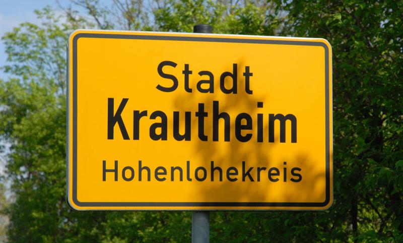 Orsteingangsschild von Krautheim, Hohenlohe ist gelb mit schwarzer Schrift. Rund herum ist grünes Laub von Bäumen. Hier sucht die Spedition LKW-Fahrer.