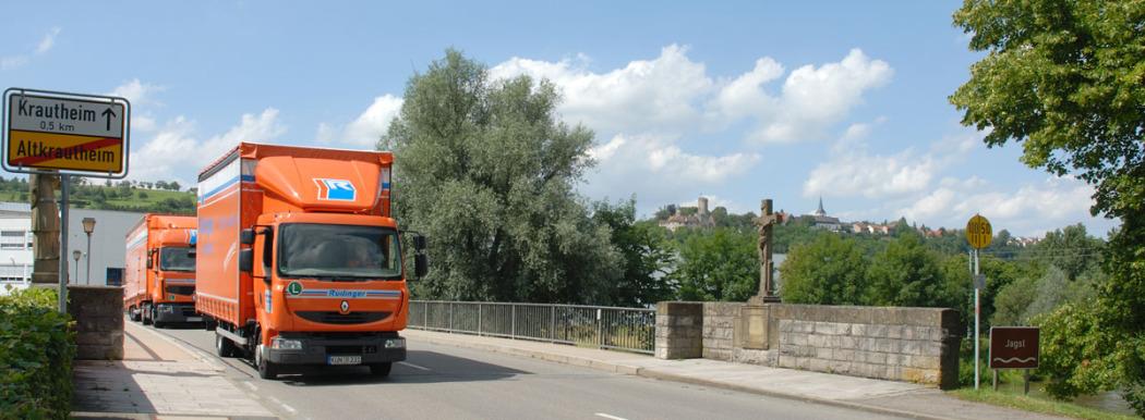 Ein kleiner orangener LKW, dahinter ein langer fahren über eine Brücke in Krautheim, Hohenlohe, Baden-Württemberg. Links das Ortsschild, unten die Straße, oben ist blauer Himmel. Hinten ist die Burg.