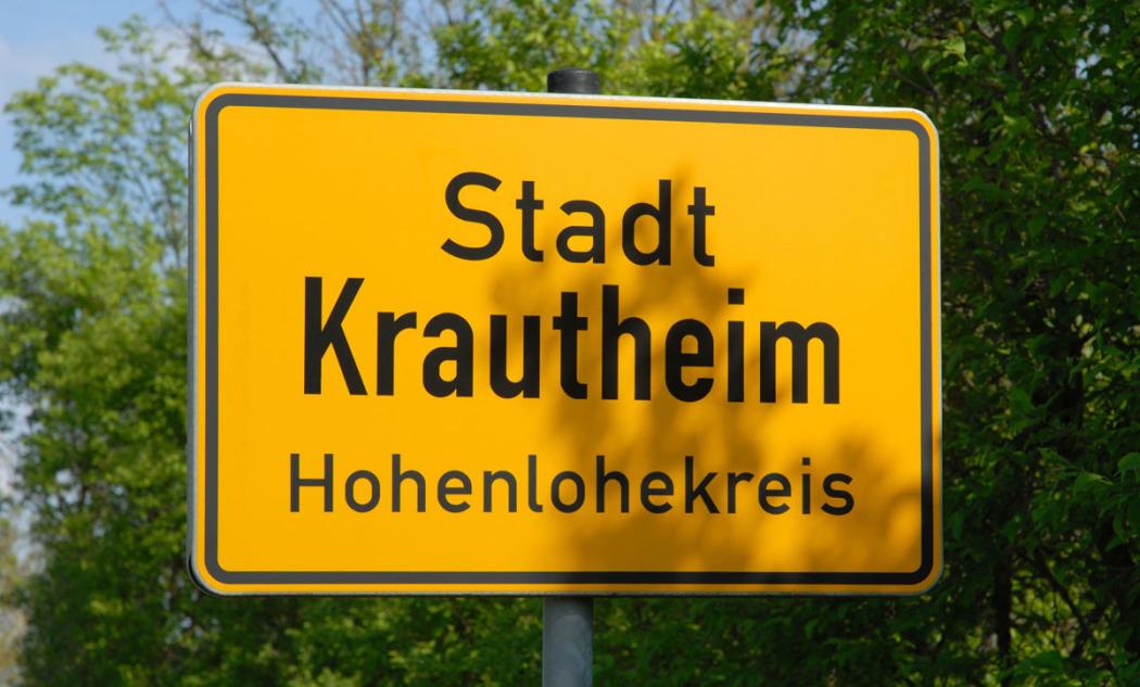 Bildfüllend ist das Ortsschild der Stadt in Baden-Württemberg zu sehen. Im Hintergrund ist hellgrünes Frühlingslaub. Auf dem gelben Schild steht Stadt Krautheim, Hohenlohekreis.