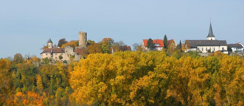 Man sieht Krautheim in Badenwürttemberg von unten, im unteren Drittel sind herbstliche Bäume, im oberen Drittel Himmel, dazwischen die Burg und die Kirche.